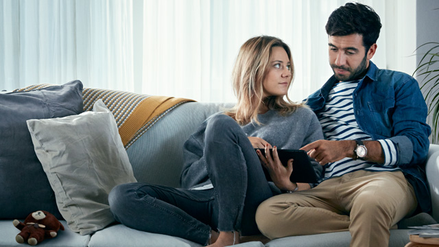 Couple sitting in sofa looking at tablet - small