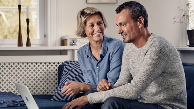 Couple home smiling with laptop - small