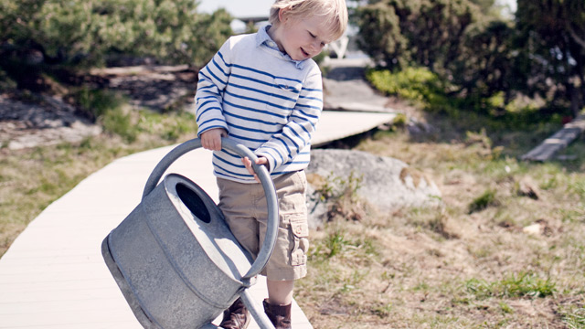 A kid with a watering can outside summertime.
